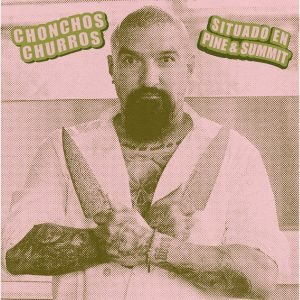 Tattooed man with goatee holding chef knives with crossed wrists